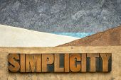 simplicity word  in vintage letterpress wood type against abstract paper landscape, minimalism conce poster