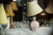 White Lamp With Shifted Shade And Other Table Lamps Behind A Lamp Store Window Glass poster