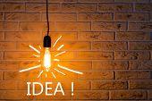 Vintage Fashionable Edison Lamp On Brick Background With An Inscription Idea . Creative Idea Concept poster