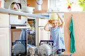 Little Adorable Cute Toddler Girl Helping To Unload Dishwasher. Funny Happy Child Standing In The Ki poster