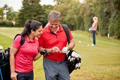 Mature Couple Playing Round Of Golf Carrying Golf Bags And Marking Scorecard poster