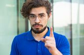 Serious Concerned Guy Pointing Index Finger Up. Handsome Bearded Young Man In Blue Casual T-shirt St poster