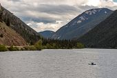 Large Lake Surface Surrounded By Tall Mountains, A Sole Person In A Kayak Rowing On The Water poster