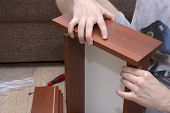 A Male Tool Collects Furniture Color Spanish Walnut. Assembly Of A Desk Drawer Cover. poster