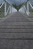 Low View Of The Bridge. Wood Paved And White Fence Bounded By A Suspension Bridge In The Donja Dubra poster