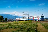 A Local Train Of Jr Izuhakone Tetsudo-sunzu Line Traveling Through The Countryside On A Sunny Spring poster
