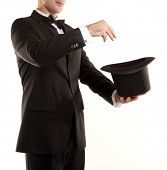 Illusionist magician is doing magic with top hat