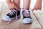 image of child development  - Child successfully ties shoes  - JPG