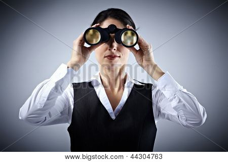 Business woman with binoculars spying on competitors.