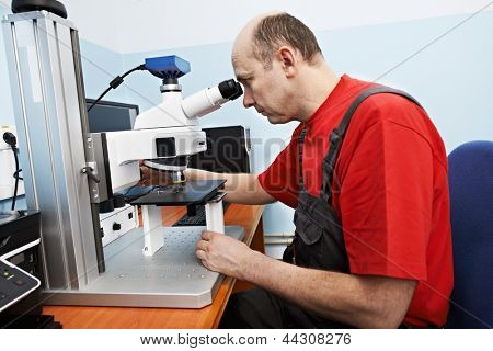 industrial worker in uniform checking quality of processed metal probe using precise optical industrial microscope