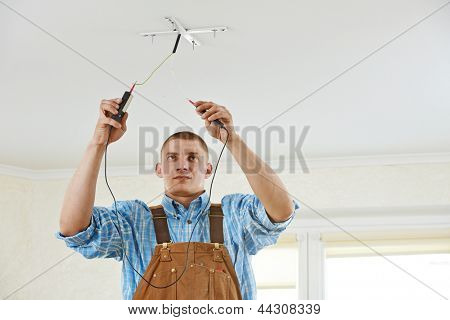 electrician working with cable checking phase of current during wiring work
