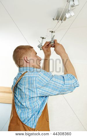 electrician working with cable mounting new wiring and ceiling lamp in home