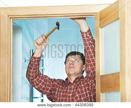 Male handyman carpenter at interior wood door installation with hammer