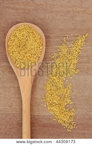 Bulgur wheat cereal in a wooden spoon over papyrus background.