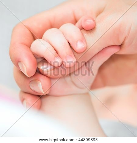 Close-up of baby's hand holding mother's finger with tenderness