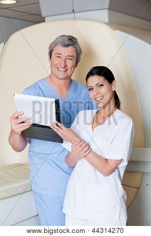 Portrait of happy multiethnic radiologic technicians holding clipboard while standing by MRI scan machine