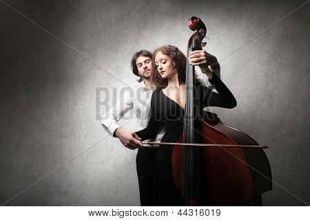 young man teaches playing contrabass to a beautiful woman