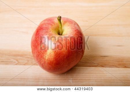 Solo la manzana roja sobre una tabla para cortar madera