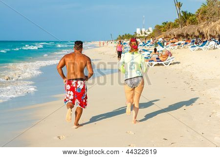 VARADERO,CUBA-APRIL 7:Tourists running at the beach April 7,2013 in Varadero.With over a million visitors per year,Varadero is the main destination for tourists visiting the island