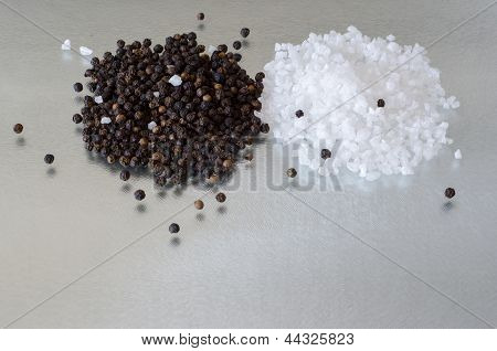 A Small Heap Of Seasalt And Peppercorns On Reflective Surface