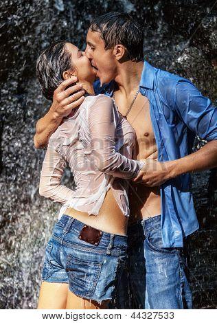 情侣拥抱和接吻在瀑布下图片