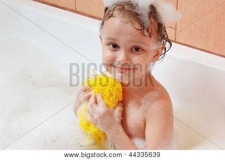Little boy with a washcloth bathes in bathroom