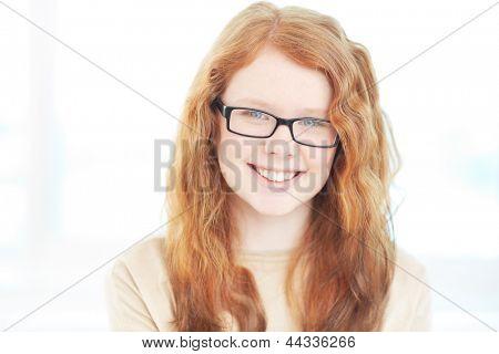 Teenage girl in eyeglasses looking at camera with smile