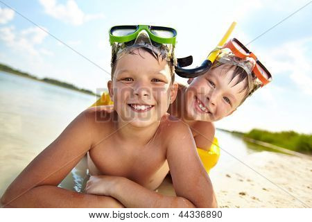 Photo of happy siblings lying on sand on summer vacation