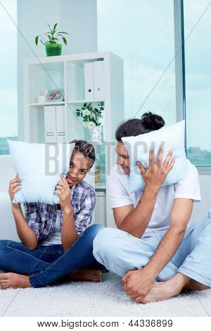 Image of guy and girl sitting on the floor with pillows by their faces