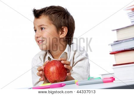 Photo of happy kid sitting at the table with red apple and looking aside