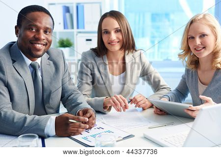 Image of three business partners looking at camera with smiles in office