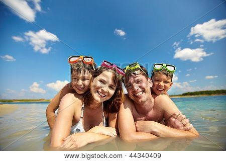 Photo of happy family of divers in water looking at camera