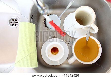 Dishwashing. White Dishes In The Kitchen Sink.