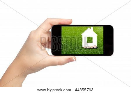 Isolated Woman Hand Holding The Phone With House On The Screen