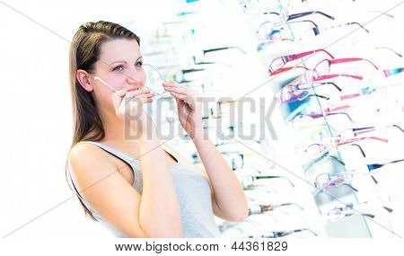 Pretty, young woman choosing new glasses frames in an optician store (color toned image; shallow DOF)