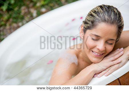 Portrait of beautiful woman enjoying a bath in a tub