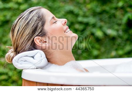 Beautiful relaxed woman in a bathtub with her eyes closed