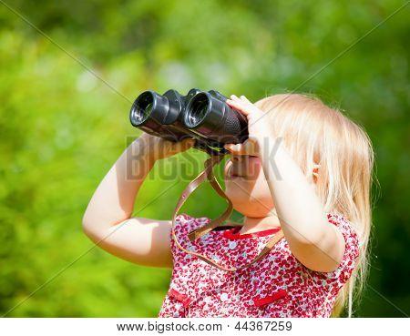 Little girl looking through binoculars outdoor