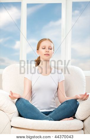 Woman Meditating, Relaxing, Sitting In A Lotus Position On The Sofa At Home