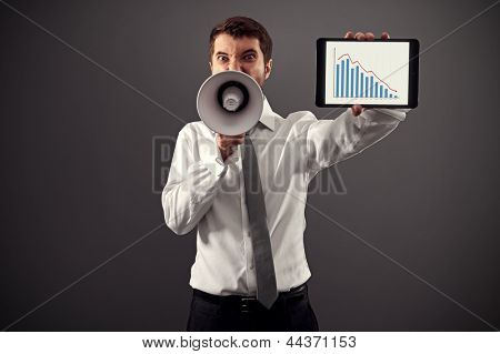 emotional businessman showing the business graph and shouting with megaphone against grey background