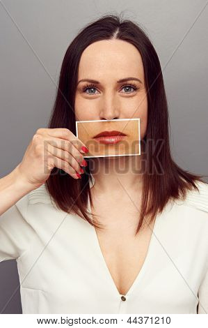 young woman covering her mouth with lips picture. studio shot over grey background