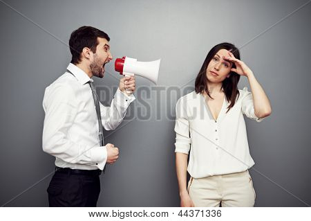 businessman screaming at the fatigued woman. studio shot over dark background