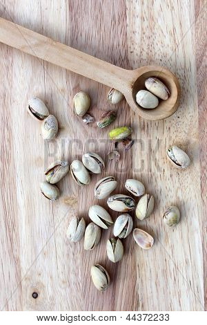 Wood spoon with pistachios on board