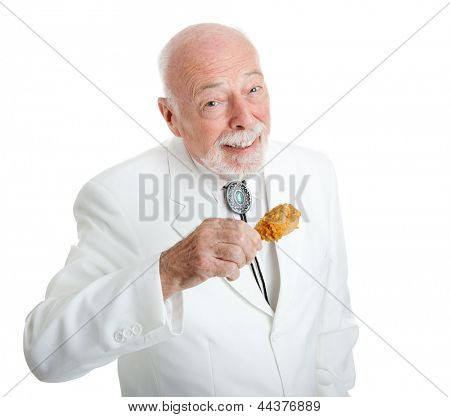 Handsome Southern gentleman eating delicious southern fried chicken.  Isolated on white.