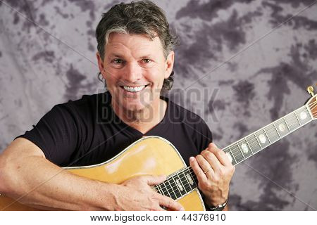 Portrait of a handsome musician with his guitar against a muslin background.