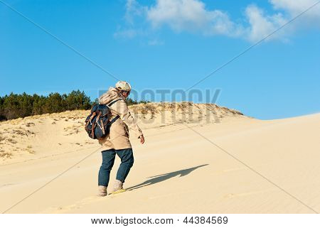 Young Woman Climbing On The Sand Dune