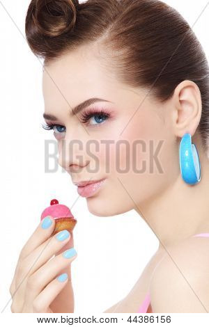 Portrait of young beautiful woman with petit four pastry in her hand, over white background