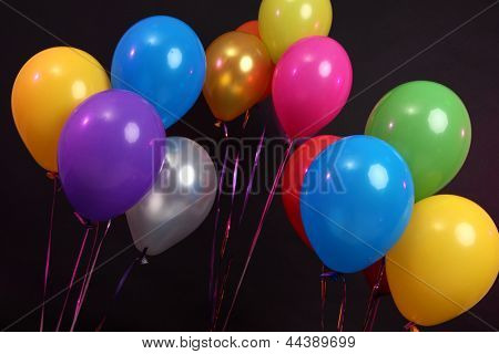 Many bright balloons isolated on black