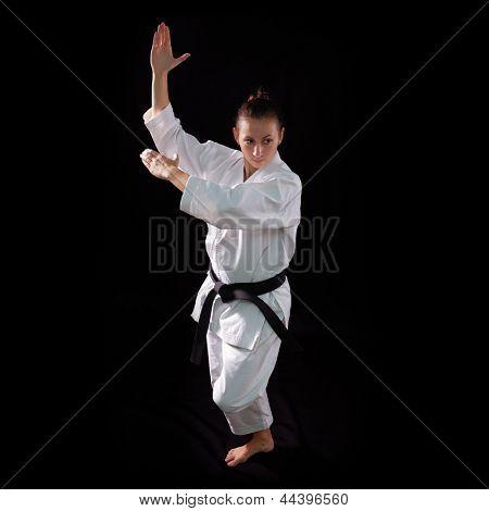 karate girl with black belt posing, champion of the world, on black background studio shot