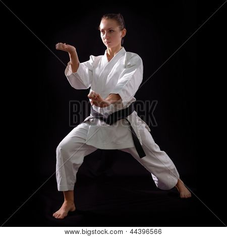 karate girl with black belt posing, champion of the world, on black background studio shot